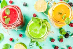 Colorful fruit and veggie smoothies. Healthy fresh fruit and veggie smoothies with ingredients on light blue concrete table, copy space top view royalty free stock photo