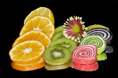 Colorful Fruits and candies. Multicolored fruits and candies  on the mirror Stock Photos