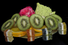 Colorful Fruits. Multicolored fruits  with the candies and rose on the mirror Royalty Free Stock Photography
