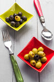 Colorful fruits olives bowls wooden table cutlery Royalty Free Stock Image