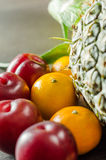 Colorful Fruits on Table. A shot of Clementines, Plums and Pineapple Stock Image