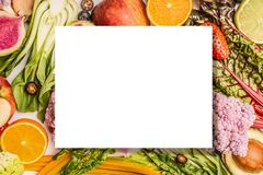 Colorful fruits and vegetables background with blank isolated sheet for your text or design , top view. Healthy food and clean eating ingredients concept Royalty Free Stock Photo