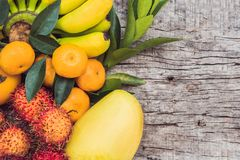 Colorful fruits on the white wooden table, Bananas, carambola, mango, papaya, mandarin, rambutan, pamela, copy space for text stock photo