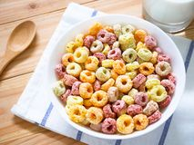 Colorful fruity breakfast cereal in a bowl. With a glass of milk on wooden background stock images