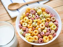 Colorful fruity breakfast cereal in a bowl. With a glass of milk on wooden background stock photography