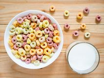 Colorful fruity breakfast cereal in a bowl. With a glass of milk on wooden background. Top view royalty free stock photos
