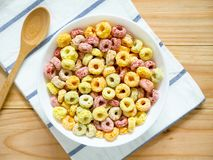 Colorful fruity breakfast cereal in a bowl. On wooden background. Top view royalty free stock photography