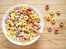 Colorful fruity breakfast cereal in a bowl. On wooden background. Top view stock image