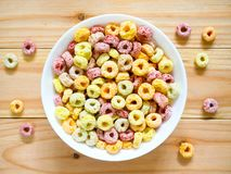Colorful fruity breakfast cereal in a bowl. On wooden background. Top view royalty free stock image