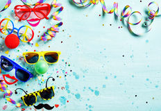 Colorful fun carnival or photo booth accessories. With assorted shaped glasses and noses, bright red lips, confetti and streamers forming a side border on light Stock Image
