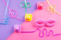 Colorful funky summer flat lay with color items. Colorful funky summer flat lay with funny items - straws, rubber ducks, lip shape glasses. Pink and purple stock photos