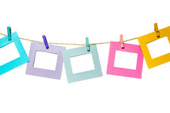 Colorful funny picture frames hanging on a rope with clothespins twine isolated. On white background royalty free stock photography