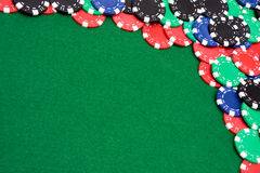 Colorful gambling chips on green felt background Stock Images