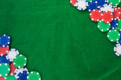 Colorful gambling chips on green felt background with copy space royalty free stock photos