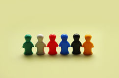 Colorful game figures. Game people symbols on yellow beige background Stock Photos