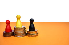 Colorful game figures symbolize a winners podium with money - with copyspace. Money winner concept with game figures - copyspace Stock Photos