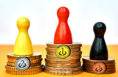 Colorful game figures symbolize a winners podium with money - with drawn medals. Concept for sport or business. Drawn medals above the figures stands for Stock Image