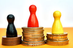 Colorful game figures symbolize a winners podium with money - macro shot. Stock Photo