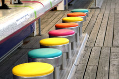 Colorful Game Stools. Row of colorful seats at a boardwalk carnival game Royalty Free Stock Photo
