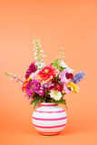 Colorful garden bouquet on orange background Stock Images