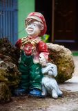 Colorful garden dwarf statue with little puppy. Colorful garden dwarf statue with little puppy Stock Images