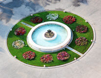 Fountain. With colorful flowers and grass from above stock images