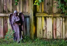 Colorful garden statuette against weathered fence stock photography