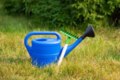 Colorful garden tools, a blue plastic watering can and rake. Stock Photography