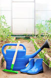Colorful garden tools. watering can, rubber boots and rake. Royalty Free Stock Image
