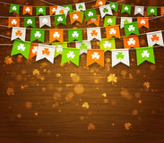 Colorful garlands of flags with clover on wood background. Saint Patrick`s Day. Colorful festive bunting with clover on wood background.Irish holiday - happy Stock Images