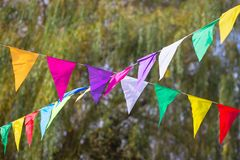 Colorful garlands with flags in the park. Colorful garlands with flags at green trees Royalty Free Stock Photos