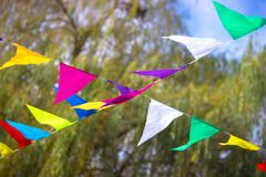 Colorful garlands with flags in the park. Colorful garlands with flags in the morning park Royalty Free Stock Images