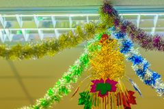 Colorful garlands are hanging on the ceiling at the office to decoration prepare for Christmas and new year party cerebration. Colorful garlands are hanging on Stock Images