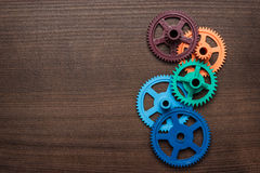 Colorful gears on the wooden background stock photos