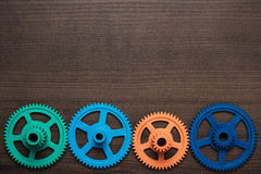 Colorful gears on the wooden background Royalty Free Stock Photo