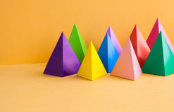 Colorful geometric abstract still life composition. Bright prism pyramid triangle shape figures. Violet yellow blue pink. Green red color objects, orange paper stock photo