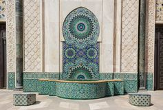 Detail of a mosque in Casablanca. Colorful and geometrical concentric mosaic arabic wall made of tile inside a fountain with pillars and arch located in The Stock Image