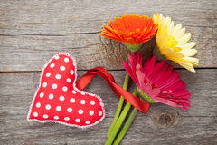 Colorful gerbera flowers and Valentine's day heart toy Royalty Free Stock Image