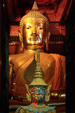 Colorful giant statue in front of big golden buddha statue backg Stock Photos