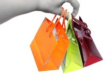 Colorful gift bags are hold by hand of young woman. Isolated on white background royalty free stock photography