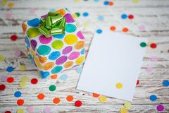 Colorful gift box with empty blank on wooden table. Holiday greeting card.  royalty free stock photos