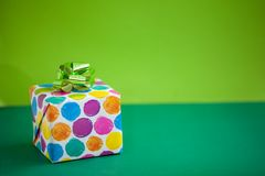 Colorful gift box on lime color background. Holiday greeting card.  stock photo