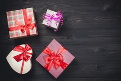 Colorful gift boxes on nice dark wooden background. Christmas or valentines day background with free space. Colorful gift boxes on nice dark wooden background Stock Images