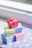 Colorful gift boxes on spotted fabric near window Royalty Free Stock Photo