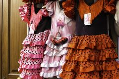 Colorful gipsy flamenco dresses on rack hanged in Spain market.  stock photo
