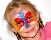 Colorful girl. A beautiful caucasian white girl child head portrait with happy smiling facial expression and a butterfly painting on her face stock image