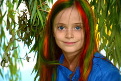 Colorful girl. Portrait of a cute teenager girl with blue contact  lenses and colorful hair in the leaves of a weeping willow Royalty Free Stock Photos
