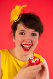 Colorful girl in red and yellow eating cupcake Royalty Free Stock Photo