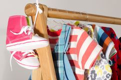 Dressing closet with clothes and baby shoes arranged on hangers. royalty free stock image