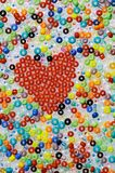 Colorful glass beads. And red heart Royalty Free Stock Photos